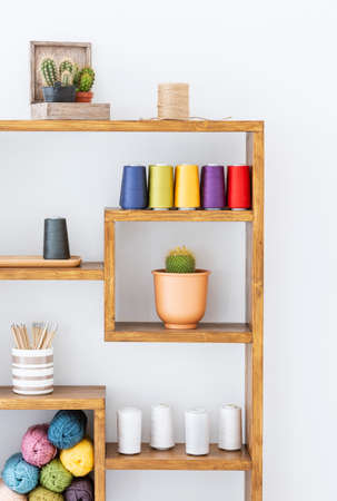Colorful yarns and plants on wooden shelves in white interior. Real photo