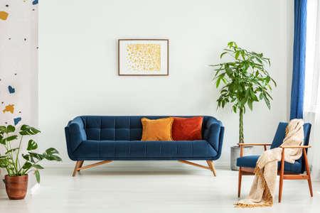 Moderne stoel uit het midden van de eeuw met een deken en een grote bank met kleurrijke kussens in een ruim woonkamerinterieur met groene planten en witte muren. Echte foto. Stockfoto