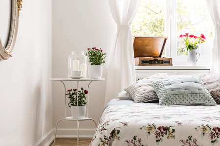 Rose loving womans bedroom interior with a bed with flower pattern bedspread and pastel gray pillows. Red roses in pots on a stand by the bed. Real photo. Фото со стока