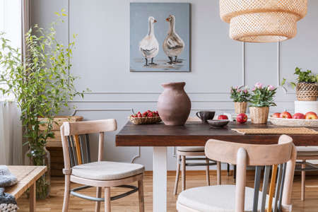 Wooden chairs at table with flowers in natural dining room interior with poster and lamp. Real photo