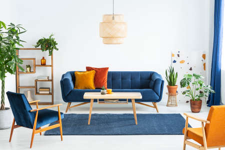Retro armchairs with wooden frame and colorful pillows on a navy blue sofa in a vibrant living room interior with green plants. Real photo. Stockfoto - 108108490
