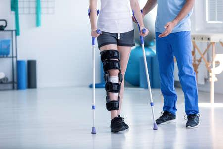 fisioterapeuta y paciente con lesión en la pierna durante la formación con muletas