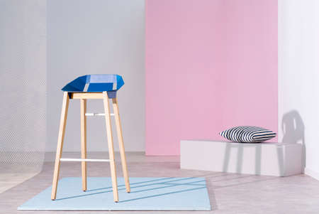 Real photo of a blue bar stool with wooden legs casting a shadow on white wall in bright studio interior