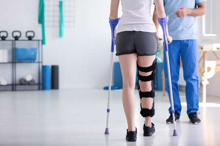 Patient with stiffener on the leg walking with crutches during rehabilitation Stockfoto
