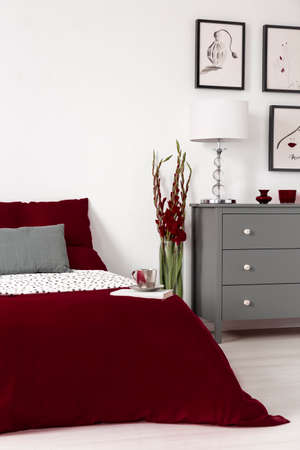 Real photo of a romantic bedroom interior with dark red sheets on a bed, flower and grey commode. Empty wall, place your poste Zdjęcie Seryjne