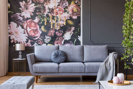 Blanket on grey couch in living room interior with flowers wallpaper and lamp on table. Real photo Stock fotó