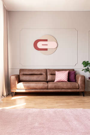 Poster above leather settee with cushions in living room interior with pink carpet and plant. Real photo Stok Fotoğraf