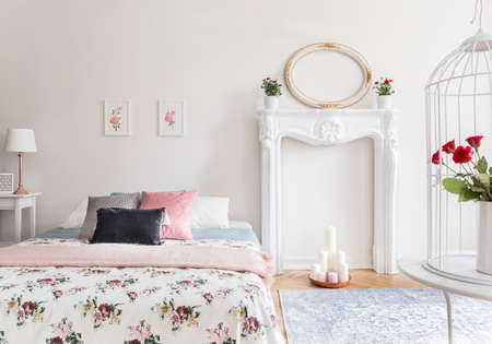 A bright bedroom interior with an English style decor. A bed and a fireplace mantel against a wall. Real photo.