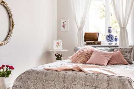 Soft gray and lemonade pink bedding and pillows on a bed which is standing against a bright window in an English style bedroom interior. Real photo. Stok Fotoğraf