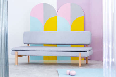 Real photo of a simple, gray couch in colorful living room interior with geometric wall decor Фото со стока