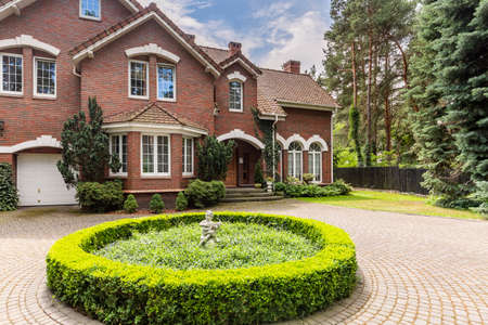 Round hedge and a small statue in the middle of a cobblestone driveway to an elegant, english style house with white windows and brick exterior 写真素材