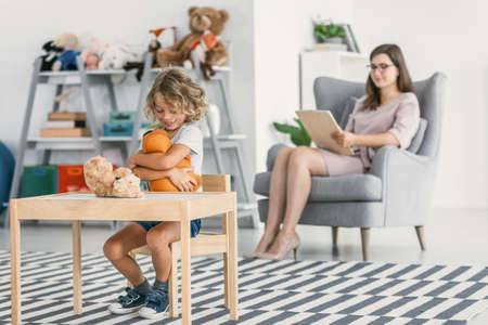 Happy autistic boy playing with a plush toy and his psychologist sitting in the blurred background holding a notepad