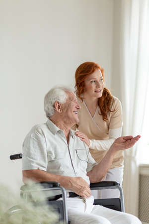 Patient in a wheelchair smiling while talking to a nurse in an old age home Stock Photo