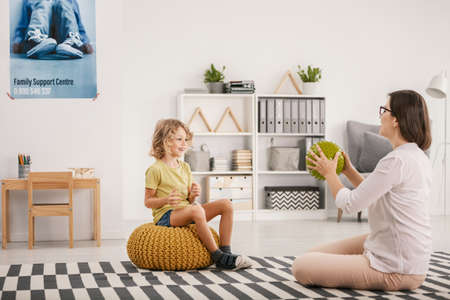 Young female therapist playing with a happy orphaned boy during a therapy session