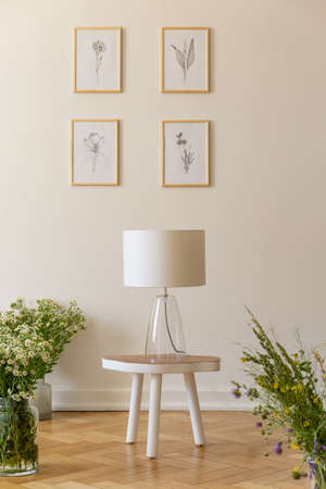 A night lamp on a stool surrounded by bunches of wild flowers against a vanilla wall with nature drawings in a wooden floor room interior. Real photo. Stockfoto