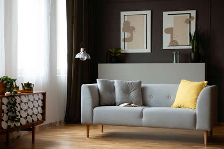 Grey lounge with yellow cushion in real photo of dark living room interior with window with drapes, retro cupboard and lamp