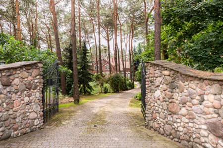 Metal gate open to a cobblestone driveway to a luxurious summer villa with brick facade in the forest