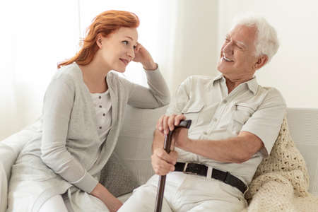 Man with a cane talking to his daughter and smiling