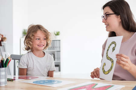 Speech therapist teaching pronunciation to a little kid using colorful pictures