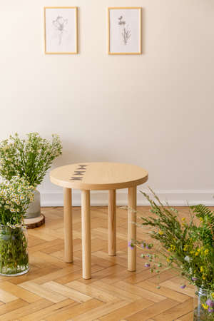 A small round wooden table surrounded by fresh meadow flowers standing on a parquet against a light beige wall with illustrations of nature in a sunny guestroom interior. Real photo.