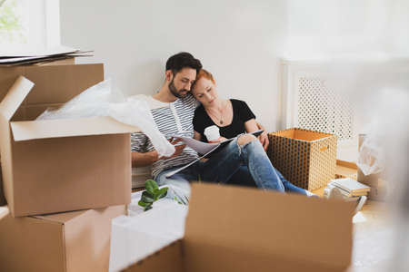 Happy marriage packing stuff into carton boxes while moving-out Standard-Bild - 108119685