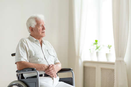 Paralyzed, elderly man in a wheelchair alone in a room Banque d'images - 108119686