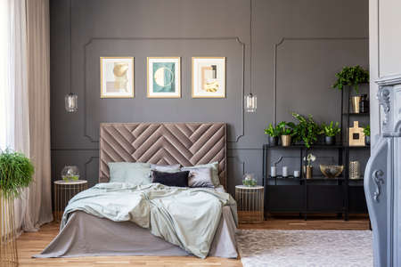 Dark bedroom interior with a comfy double bed, posters, black shelf and wall molding