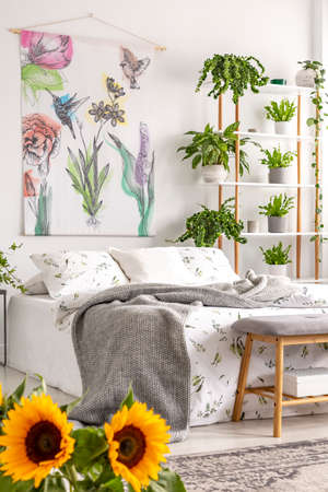 Urban jungle bedroom interior with sunflowers in the foreground and many green plants beside a bed dressed in white bedding. Tapestry on the wall. Real photo.