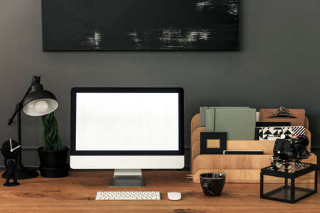 Lamp and organizer on wooden desk in grey home office interior with mockup. Real photo