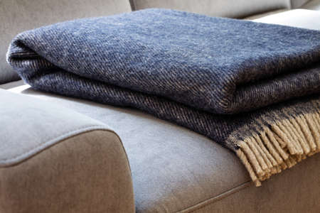 Close-up of a warm, navy blue, wool blanket with beige fringe on a comfy, gray sofa in a cozy living room interior 스톡 콘텐츠