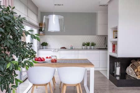 Spacious, open space kitchen interior with white cupboards and a dining area with a wooden table and plastic chairs. Real photo