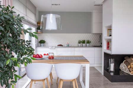 Ruim, open keukeninterieur met witte kasten en een eethoek met een houten tafel en plastic stoelen. Echte foto