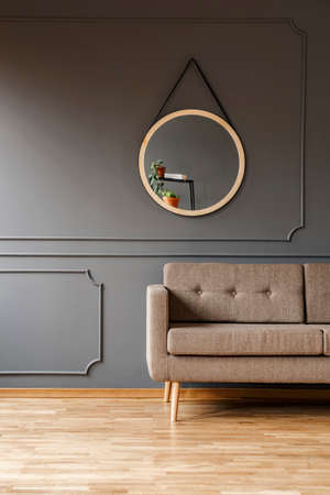 A round mirror above a simple, elegant brown sofa and a place for a side table in a fancy living room interior. Real photo. Stock Photo
