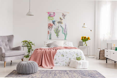 Nature lovers bright bedroom interior with a wall art of flowers and birds painted on a fabric above a bed which is dressed in green plants pattern on white linen. Real photo. Фото со стока