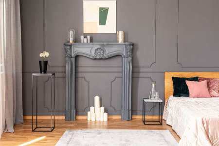 Elegant bedroom interior with a candles set in a fireplace portal, metal tables, wall molding and bed Stock Photo