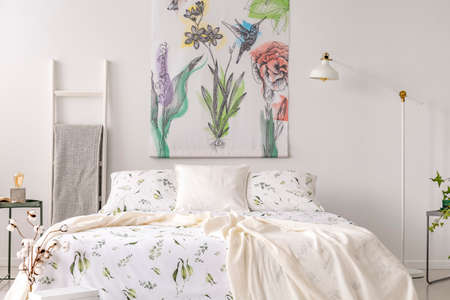 A pastel bedroom interior with a bed dressed in green plants pattern white linen. Fabric painted in flowers and birds on the background wall. Real photo.