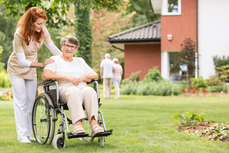 A professional female caregiver with her impaired geriatric patient on a wheelchair outside in the garden. Stockfoto