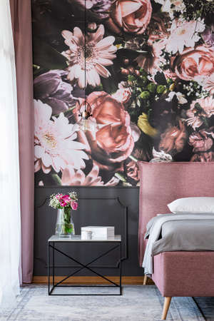 Flowers on table next to pink bed in bedroom interior with patterned wallpaper. Real photo