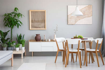 Real photo of bright dining room interior with wooden table and four chairs, posters with fabrics, fresh plants placed on wooden platform and cupboard with decor