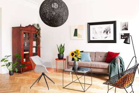 Gallery of pictures on a white wall above a cozy couch with colorful pillows in a stylish living room interior with herringbone parquet floor.