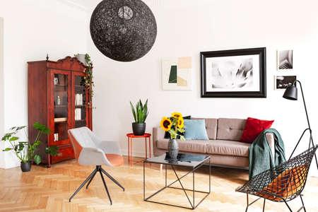 Galerij van foto's op een witte muur boven een knusse bank met kleurrijke kussens in een stijlvol woonkamerinterieur met visgraatparketvloer. Stockfoto