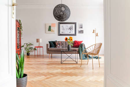 View through an open door into a spacious, unique living room interior with eclectic furniture and hardwood floor.