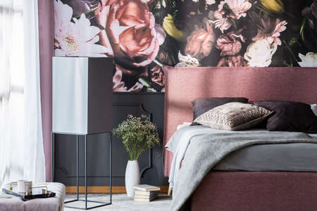 Flowers and books next to pink bed with grey pillows in patterned bedroom interior. Real photo Stock fotó