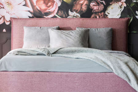 Grey blanket and cushions on pink bed in feminine bedroom interior with flowers wallpaper. Real photo Stock fotó