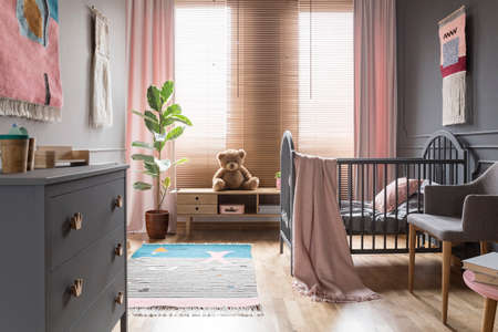 Teddy bear on wooden cupboard next to ficus in childs bedroom interior with cradle. Real photo