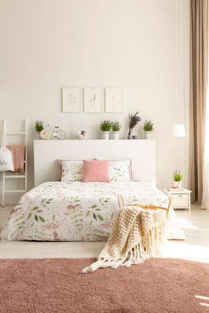 Blanket and pillows on bed with plants on headboard in pink and white bedroom interior. Real photo