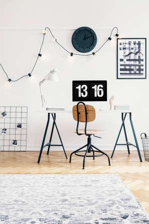 Industriestuhl und Schreibtisch mit einem Computer in einem Arbeitsraum eines Schwarzweiss-Hipster-Interieurs für einen Teenager. Echtes Foto. Standard-Bild