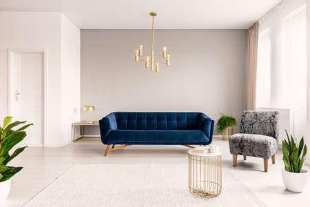 Kopieren Sie das Wohnzimmer mit einer dunkelblauen Couch, einem grauen Sessel und goldenen Akzenten. Echtes Foto. Standard-Bild