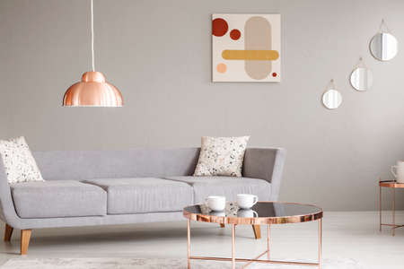 Real photo of a simple sofa, copper lamp and table, and painting on a wall in a living room interior