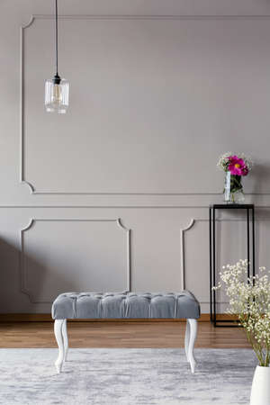 Grey hallway interior with a bench, lamp and flower in a vase on a stand. Real photo. Place for your poste